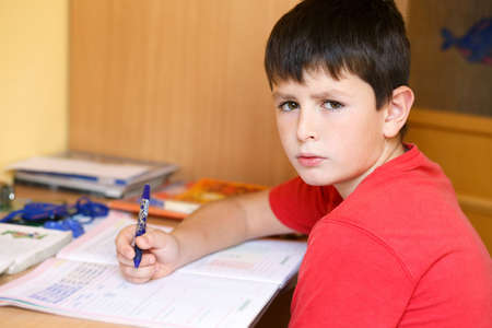 boy doing school homework, is tired and bored photo