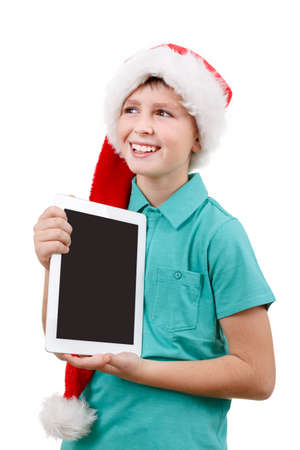 smiling teenage boy with santa claus hat isolated on white and showing his new digital tablet  photo