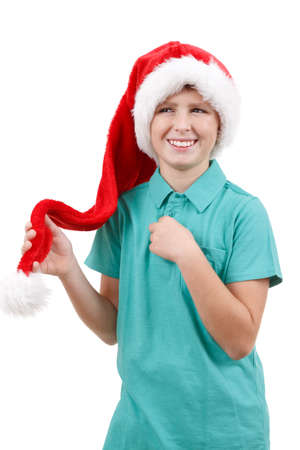 happy smiling teenager weared to red santa claus hat isolated on white photo