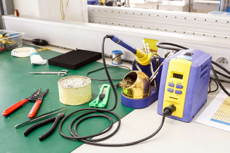 electronics equipment assembly workplace with solder and necessary tools
