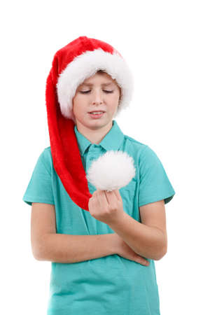 happy smiling teenager weared to red santa claus hat looking at a pompon isolated on white photo