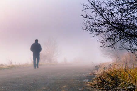 A person walk into the misty foggy road in a dramatic sunrise scene with abstract colors Stock Photo
