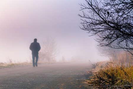 Een persoon loopt in de mistige mistige weg in een dramatische zonsopgang scène met abstracte kleuren Stockfoto