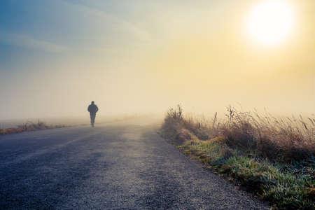 Une personne marche sur la route brumeuse brumeux à une mystique scène de lever de soleil spectaculaire avec des couleurs abstraites