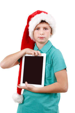 teenage boy with santa claus hat isolated on white and showing his new digital tablet photo