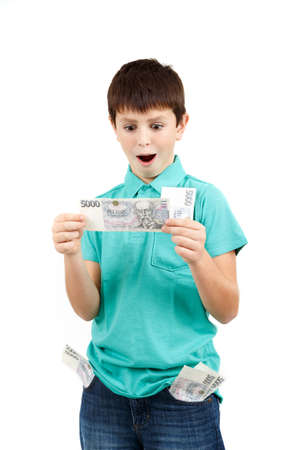 amazed boy looks at the bill from czech crown banknotes