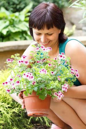 happy smiling middle age woman gardening, offsets the flowers in a pot photo