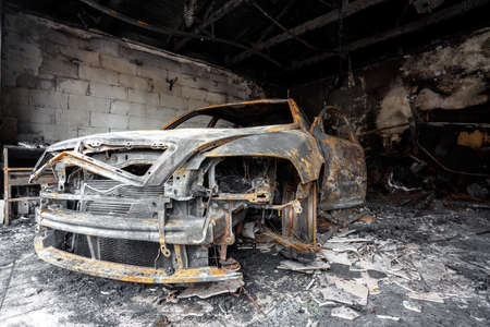 Close up photo of a burned out car in garage after fire for grunge use 写真素材