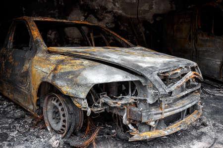 グランジの使用のための火の後で燃え尽きた車はガレージの写真を閉じる