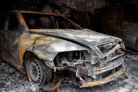 Close up photo of a burned out car in garage after fire for grunge use Standard-Bild