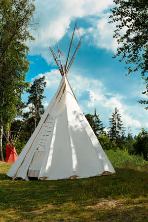 tipi: A tipi (also tepee and teepee) is a conical tent, traditionally made of animal skins, and wooden poles against blue sky Stock Photo