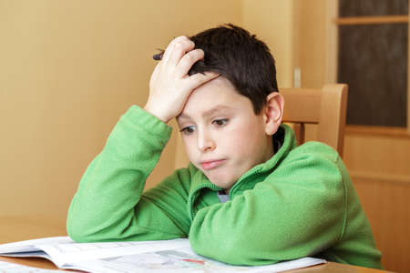 worl: bored and tiredboy doing homework from school in workbook using worl map