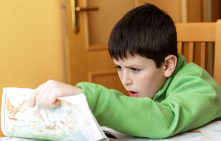 worl: bored and tired boy doing homework from school in workbook using worl map