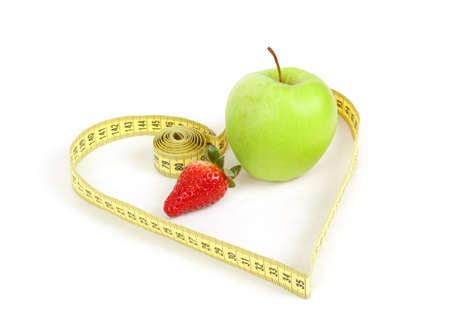green apple and strawberry with a measuring tape and heart symbol isolated on white background  photo