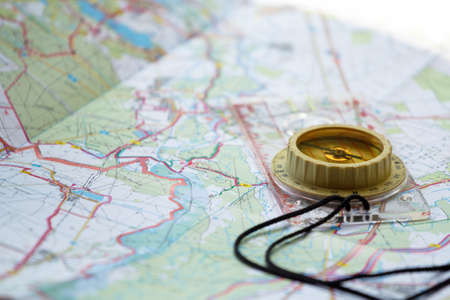 old touristic handheld compass on detailed territory map  Stock Photo