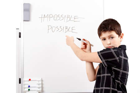 young boy student in a classroom writing possible on a empty whiteboard photo