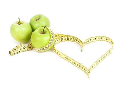 green apple with a measuring tape and heart symbol isolated on white background photo