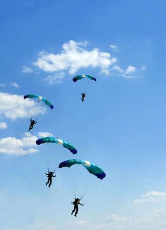 青い空に正体不明のスカイダイバー 写真素材