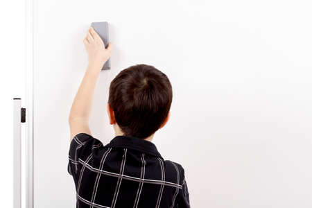 young boy student in a classroom erasing white board photo