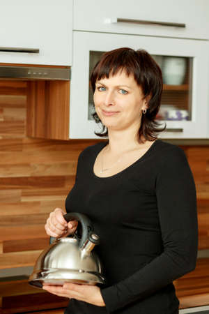 median age: middle-aged woman preparing coffee in the kitchen with kettle