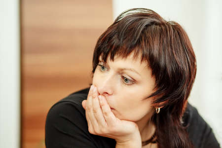 beautiful middle age tired woman holding head, looking out photo
