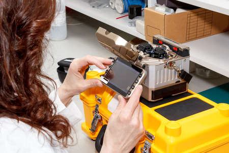 fusion: woman working with fiber optic fusion splicer in laboratory Stock Photo