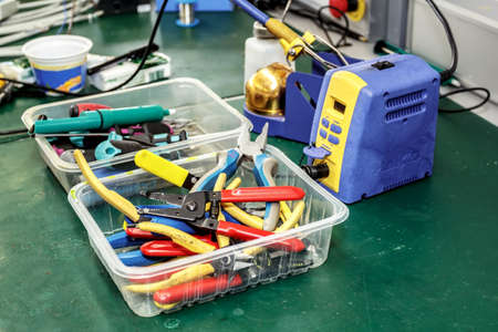 electronics equipment assembly workplace with pliers and necessary tools photo