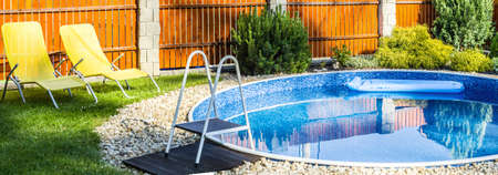 yellows: panorama of small home swimming pool with yellows sun loungers Stock Photo