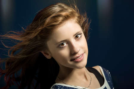 Studio fashion portrait of young beautiful girl with nice eyes on dark blue background with wind from fan in hair