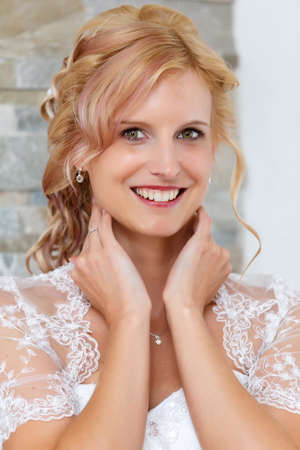 clothe: home portrait of beautiful blonde smiling bride dressed to white clothe Stock Photo
