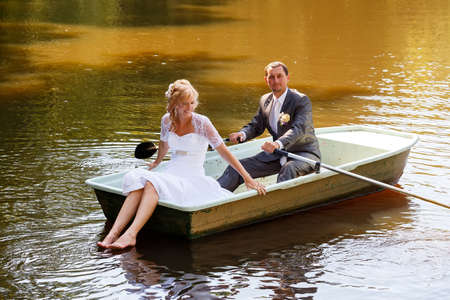 beautiful young wedding couple, blonde bride with flower and her groom just married on small boat at pond with evening sun photo