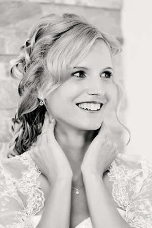 clothe: home portrait of beautiful blonde smiling bride dressed to white clothe black and white tone
