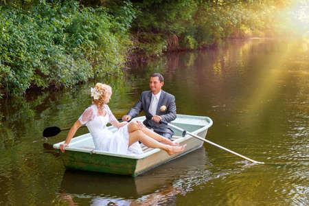 mooie jonge bruidspaar, blonde bruid met bloem en haar bruidegom net getrouwd op kleine boot op vijver met avondzon