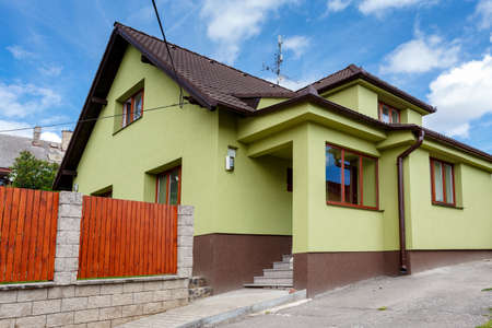 repaired rural house, fixed facade, insulation and painted to green  color photo
