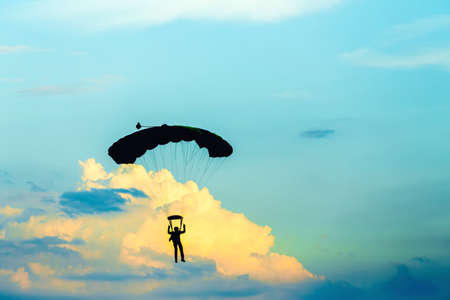 paradglider: silhouette of unidentified skydiver parachutist on blue sky on sunset Stock Photo