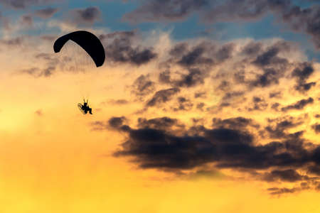 parapendio: silhouette of unidentified skydiver parachutist on sky with sunset