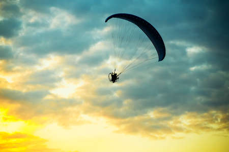 silhouette of unidentified skydiver parachutist on blue sky on sunset photo