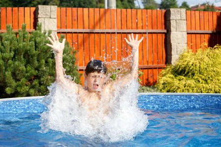 Boy jumping in the home garden swimming pool with clear water photo