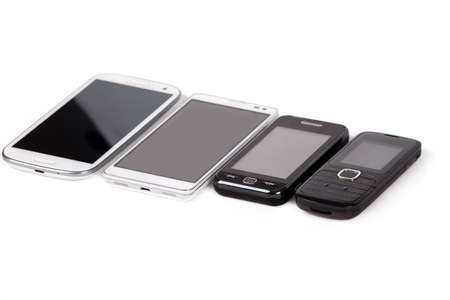 collection of cell phones, old design and new smart phones isolated on white photo