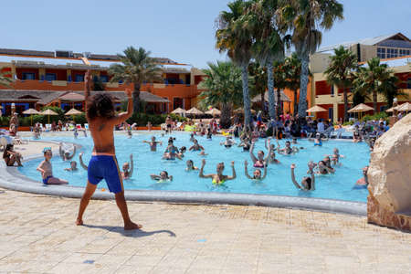 BORJ CEDRIA, TUNISIA - AUGUST 7: Tourists on holiday in an expensive hotel Carribean World are doing water aerobics in pool August 7, 2014 Borj Cedria, Tunisia.