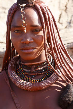 NAMIBIA, KAMANJAB, OCTOBER 10: Himba tribe woman with ornaments on the neck, in the village of Himba people near Kamanjab in northern Namibia, August 10, 2014, Namibia