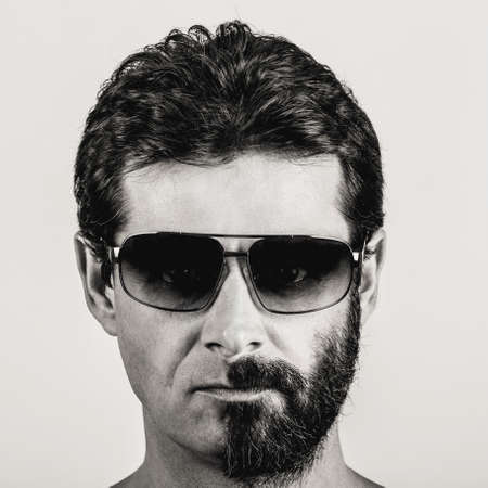 double glass: split personality - black and white portrait of man with half shaved face and sun glasses