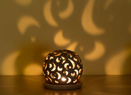 lightbeam: christmas lantern with candle in the darkness and shaddows on wall
