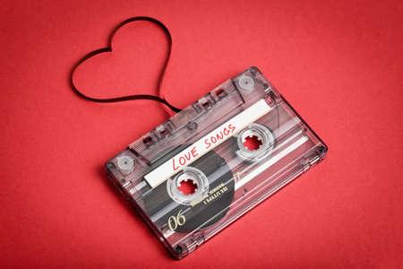 赤い背景のオーディオ カセット テープ。心臓、バレンタインはがきを形作るフィルム。ラベル テキストの愛の歌。 写真素材