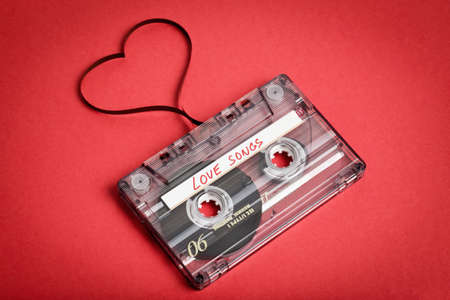Audio cassette tape on red backgound. Film shaping heart, Valentine postcard. Label text love songs. Stock Photo
