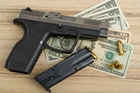 criminality: detail of gun with bullet on US dollar banknotes, crime or corruption concept Stock Photo