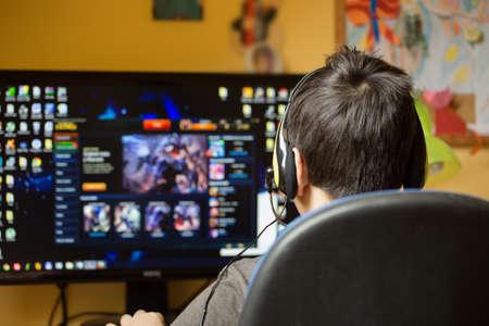 Tiener met behulp van de computer thuis met een koptelefoon, spelen spel in zijn kind kamer Stockfoto - 38483634