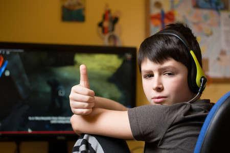 10 代のヘッドフォンで自宅のコンピューターを使用して彼の子供部屋でゲームをプレイ 写真素材