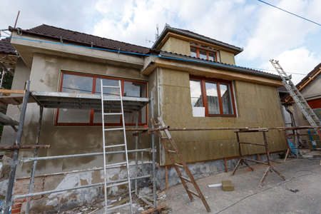 Construction or repair of the rural house, fixing facade, insulation and using color for new look 免版税图像 - 38483662