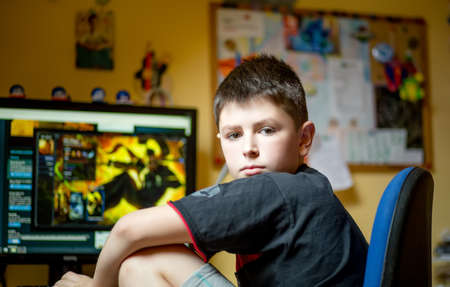 Teenager using computer at home with headphones, play game in his child room